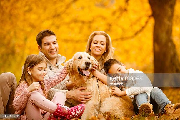 Family playing with dog in autumn park
