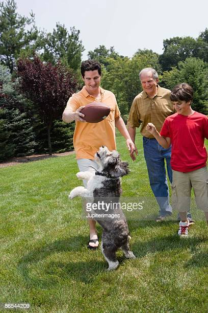Family playing with jumping dog