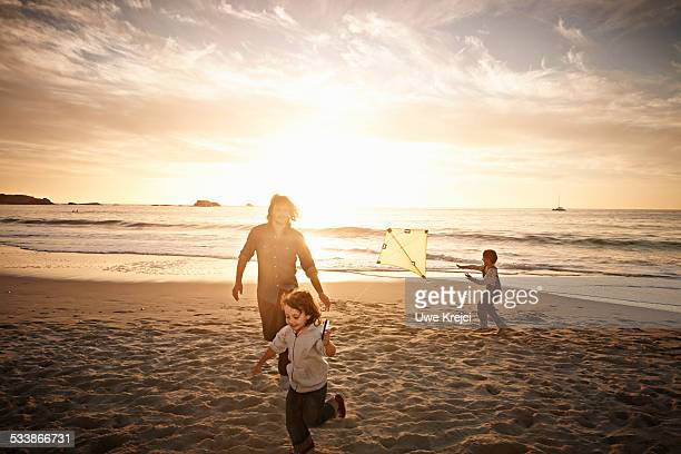 Family playing with kite on beach