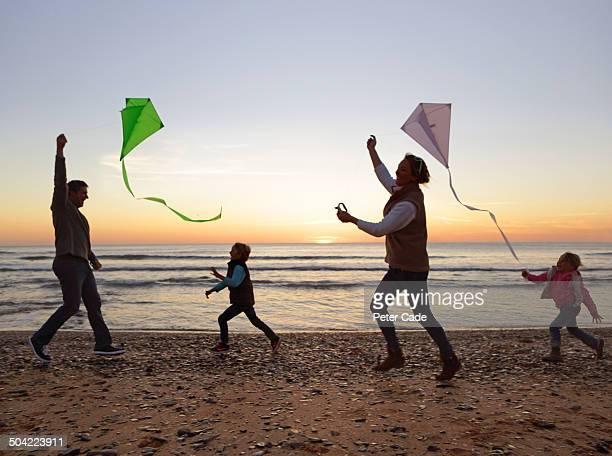 Family playing with kites on beach at sunset