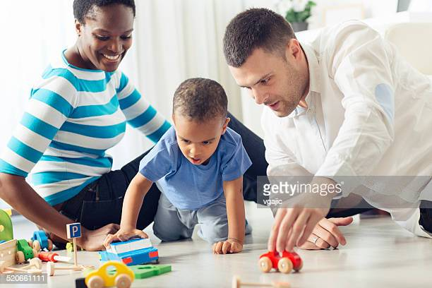 Family Playing With Little Boy At Home.