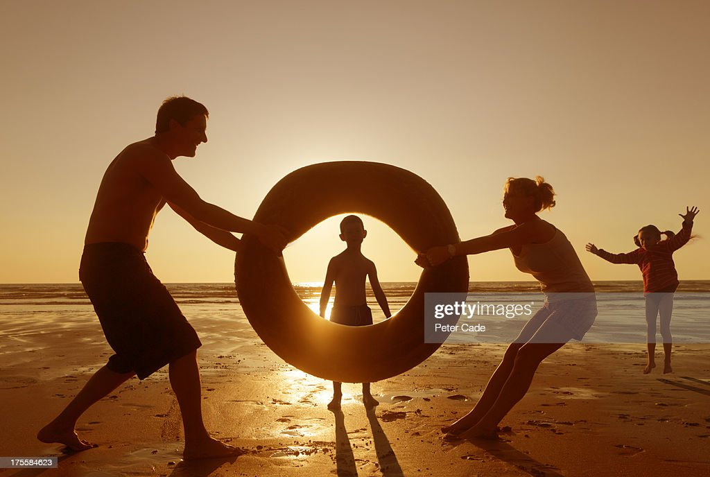Family playing with rubber ring on beach : Stock Photo