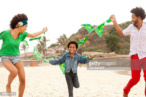 Family playing with string of flags on beach, Rio de Janeiro, Brazil