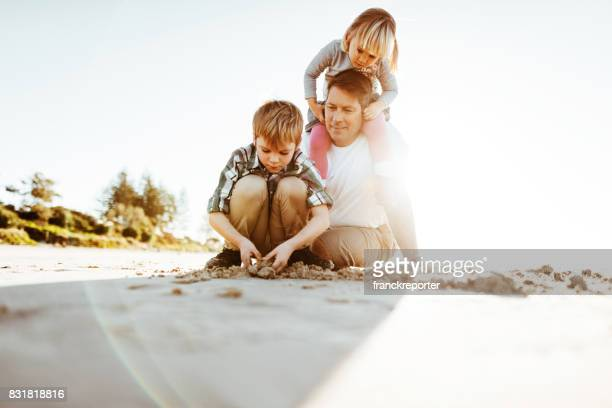 family playing with the sand on the beach