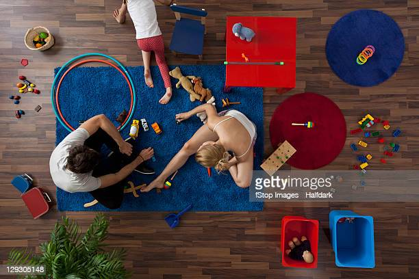 A family playing with toys in their living room, overhead view