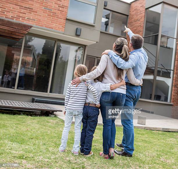 Family pointing at their house