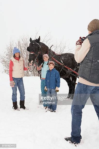Family portrait by horse in snow