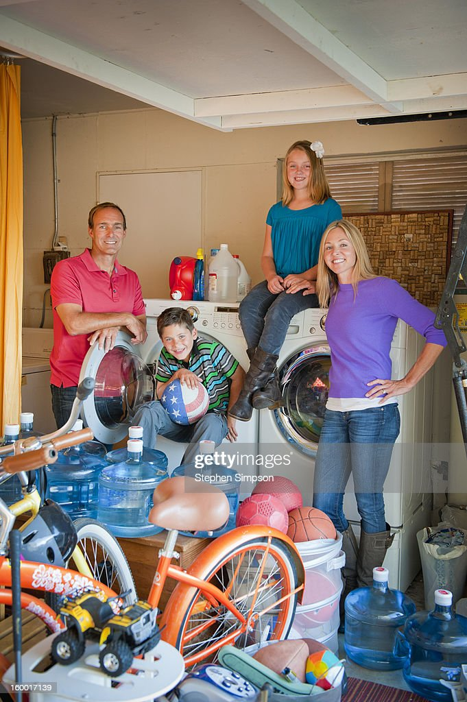 family portrait in cluttered garage/laundry room : Stock Photo
