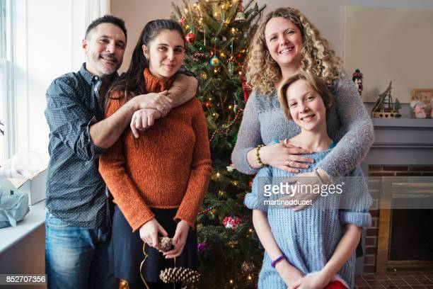 Family portrait in front of Christmas tree at home.