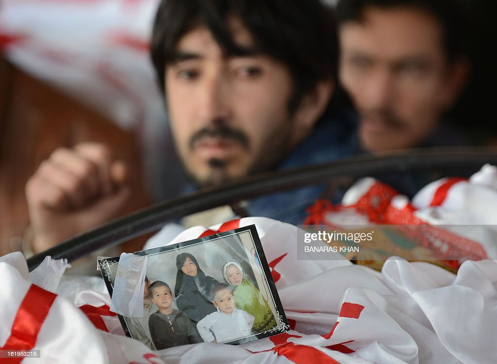 A family portrait is pictured on a coffin as Pakistani Shiite Muslims gather around the coffins of bomb attack victims on the second day of protests following the blast in Quetta on February 18, 2013. Thousands of women refused Monday to bury victims of a bloody bombing and a strike shut down Pakistan's biggest city Karachi as protesters across the country demanded protection for Shiite Muslims. AFP HOTO/Banaras KHAN