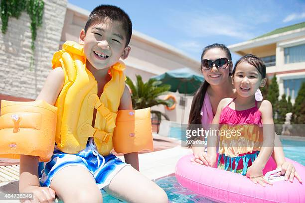 Family portrait, mother, daughter, and son, by the pool with pool toys