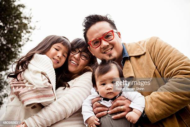 Family portrait of mid adult couple with daughter and baby boy in park