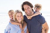Parents giving piggyback ride to kids at beach. Close up of smiling family having fun at summer vacation. Portrait of happy family looking at camera at beach.