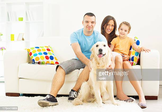 Family portrait with dog relaxing at home.