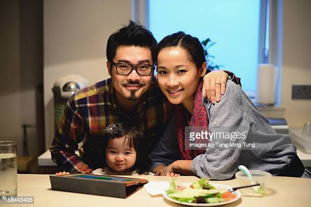 Family portrait with mom dad & baby at home