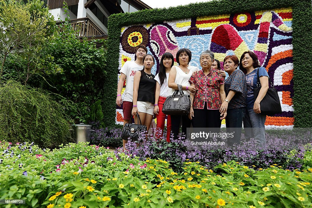 Family pose for a photograph in front a giant snake-themed floral display at the Sentosa Flowers exhibition at Palawan Beach on February 11, 2013 in Singapore. Millions of spring flowers decorate the island in celebration of the Chinese New Year, the year of the Snake.