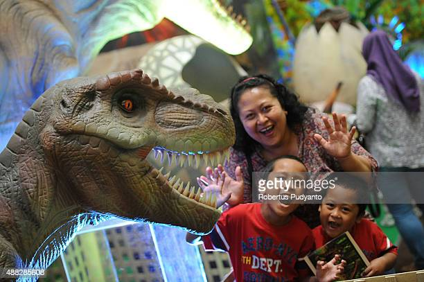 A family pose near TRex replica in the Dinosaur Adventure and Learning Experience Park at Tunjungan Plaza on September 15 2015 in Surabaya Indonesia...