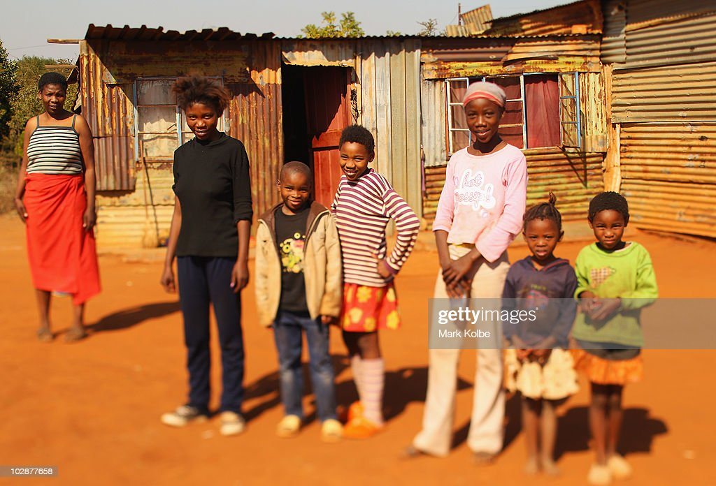 A family pose outside a shanty house on June, 2010 in Rustenburg, South Africa.
