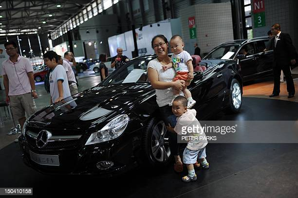 A family poses for a photo next to a Mercedes convertable sports car on display at the Pudong Auto Show in Shanghai on August 17 2012 Growth in...