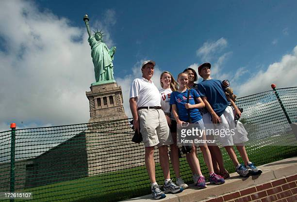 A family poses for a picture in front of the Statue of Liberty on the first day it is open to the public after Hurricane Sandy on July 4 2013 on the...