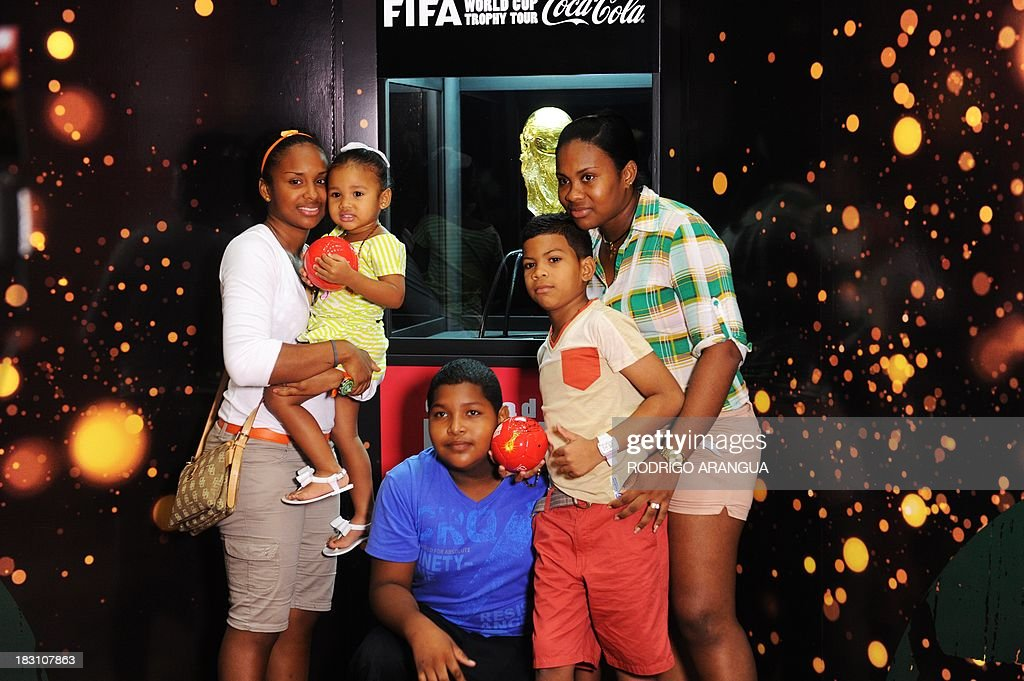 A family poses next to the FIFA World Cup in Panama City, on October 4, 2013. The Cup is in Panama for two days as part of a tour to exhibit it in 89 countries before the beginning of the FIFA World Cup Brazil 2014. AFP PHOTO/ Rodrigo ARANGUA