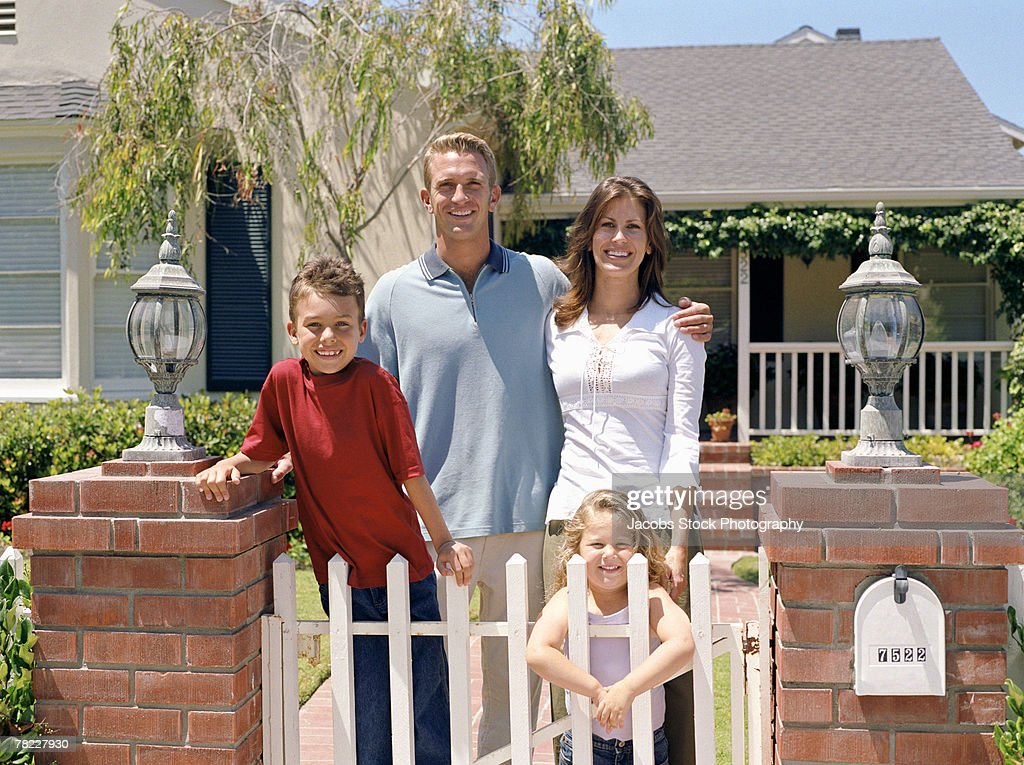 Family posing at gate : Stock Photo