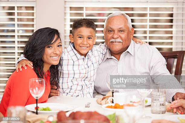 Family posing with grandfather for holiday photo. Dinner table.