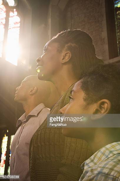 Family Praying in Church With Sunlight From Window
