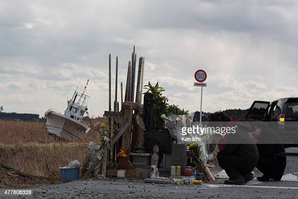 A family prays for tsunami victims at ukedo area on March 11 2014 in Fukushima Japan On March 11 Japan commemorates the third anniversary of the...