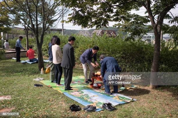 A family prepares to perform a ceremonial offering to relatives in North Korea near the Demilitarized Zone at Imjingak on October 4 2017 South Korea...
