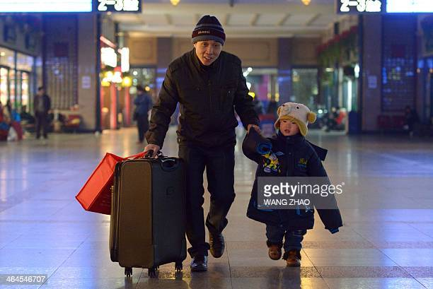 A family prepares to take a train at a railway station in Beijing on January 23 2014 The world's largest annual migration began on January 16 in...