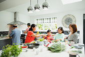 Three generation family are preparing vegetables for a stir fry in the kitchen of their home together.