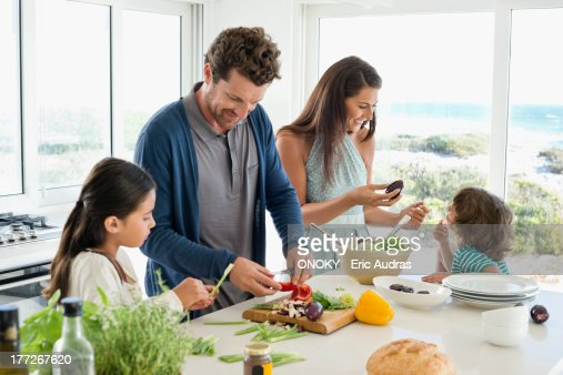 Family preparing food in the kitchen : Stock Photo