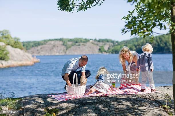 Family preparing for picnic beside lake