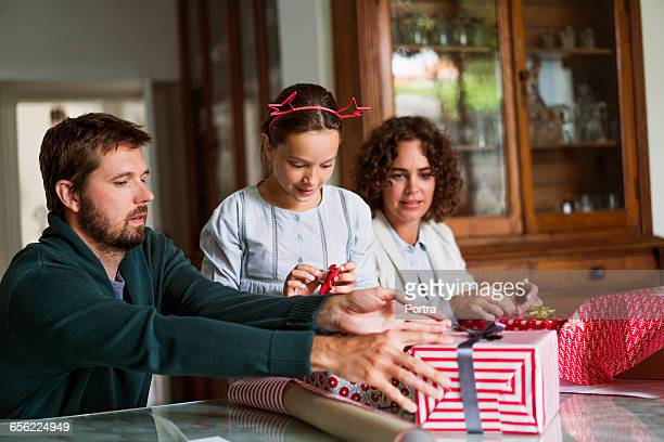 Family preparing gift boxes during Christmas