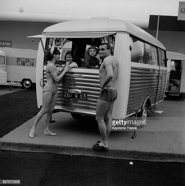 A family presents a model of camping because during the Camping caravaning and sports' fair at the Exhibition Palace at the Porte de Versailles on...