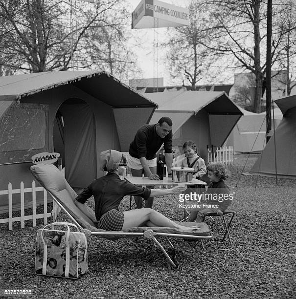 A family presents a model of tent and camping equipment at the Camping caravaning and sports' fair at the Exhibition Palace at the Porte de...