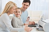 Family printing pictures with laptop