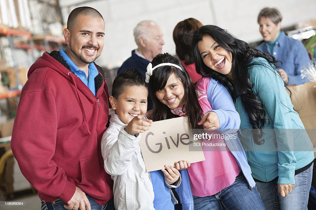 Family promoting giving at a donation drive : Stock Photo