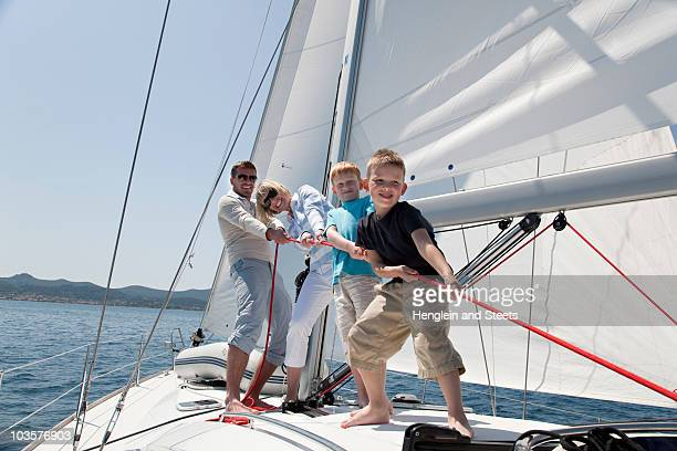 Family pulling rope on yacht