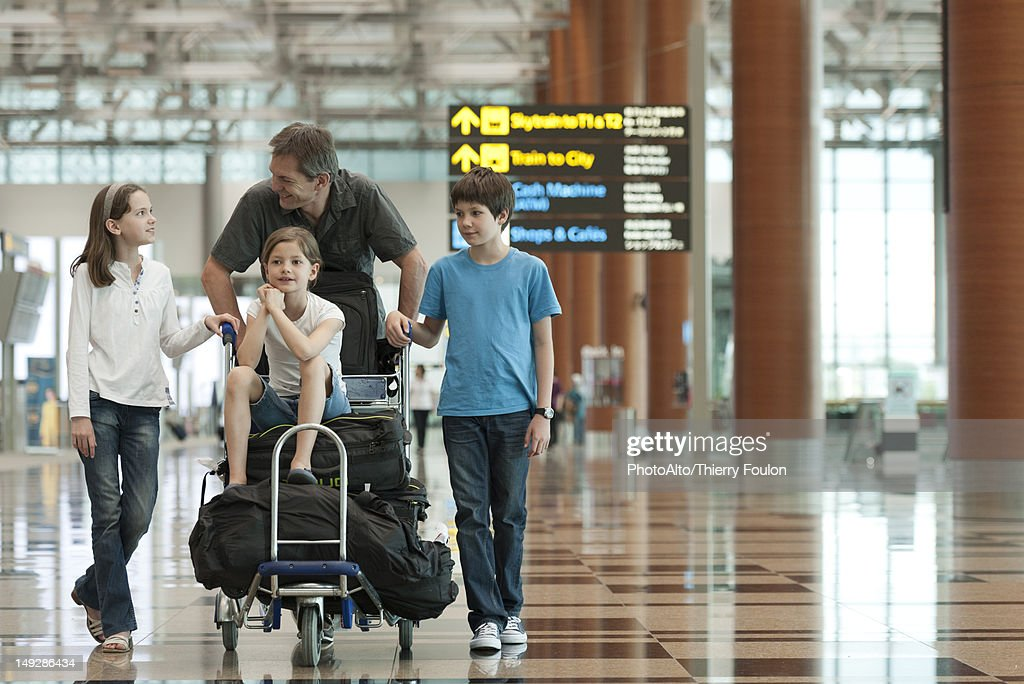 Family pushing luggage cart in airport : Stock Photo