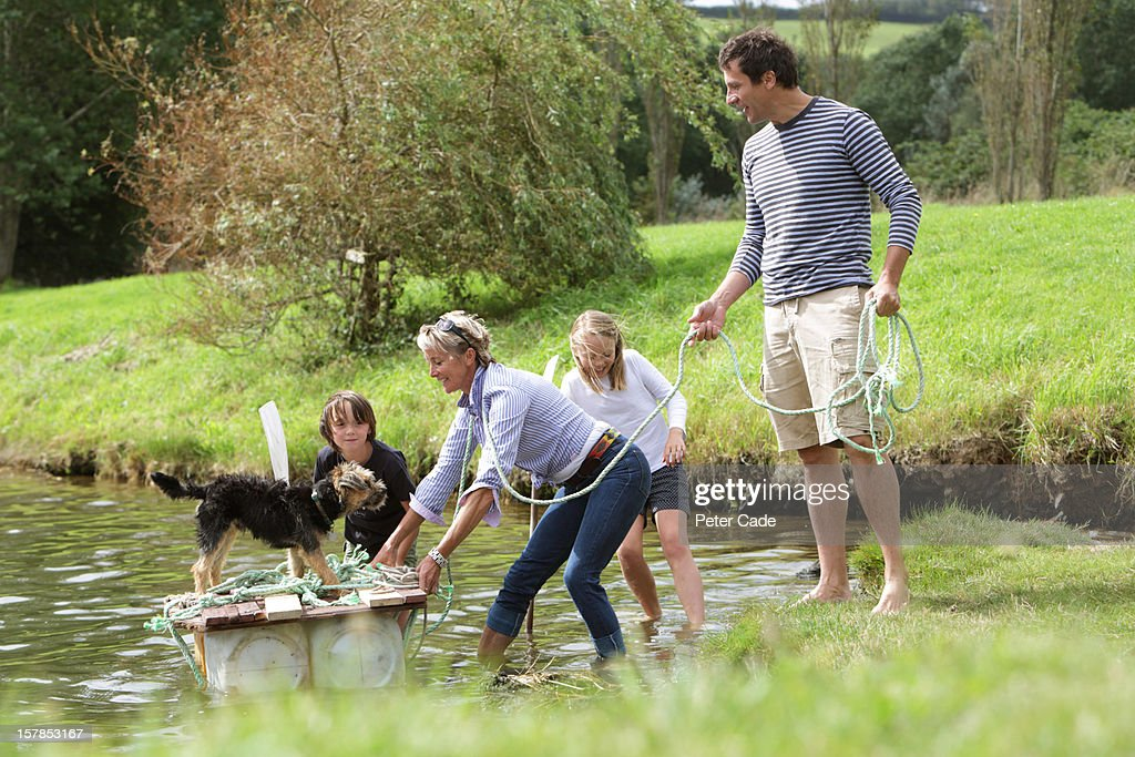Family putting home made raft into water : Stock Photo
