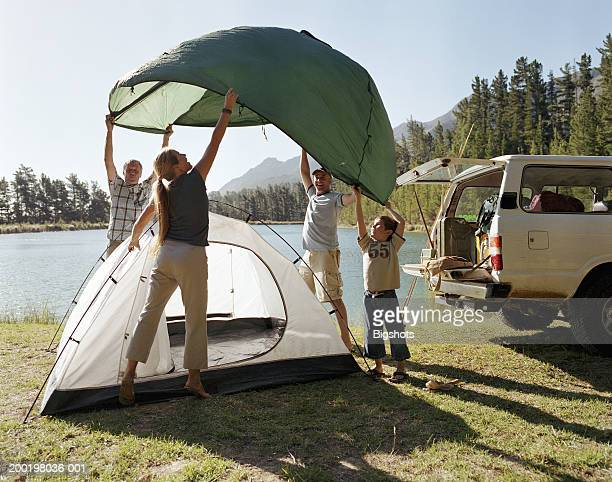Family putting up tent by lake