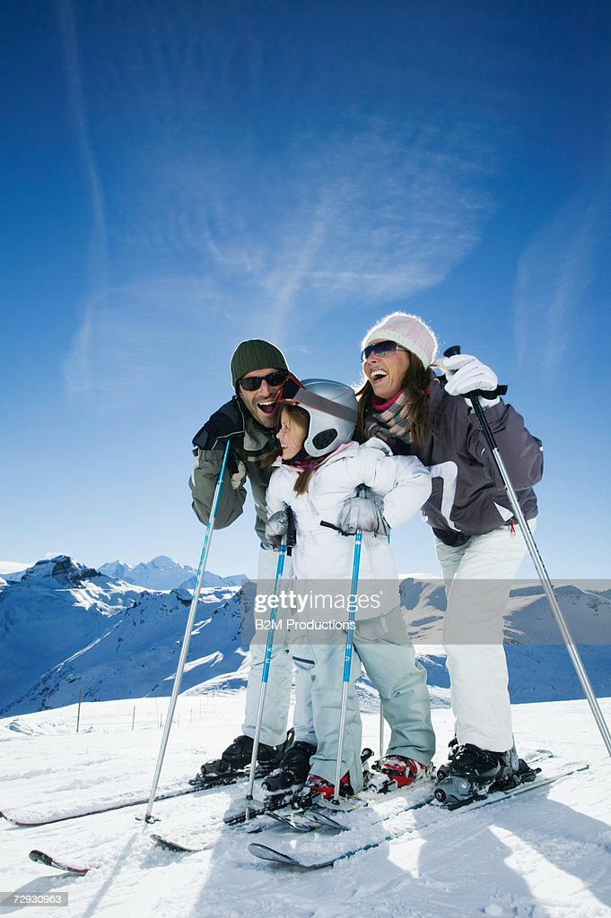 Family qwith one child (6-8) on ski slope : Stock Photo
