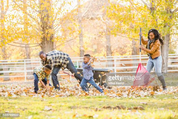 Family raking autumn leaves together