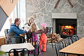 A family relaxes in a warm ski lodge