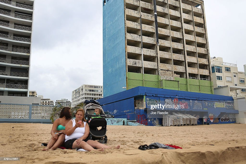 A family relaxes on the beach near the shell of a building on July 1 2015 in San Juan Puerto Rico The island's residents are dealing with increasing...