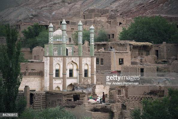 A family relaxes on the roof of the family house on June 11 2007 about 70 kilometers east of Turpan in Tuyoq China The ancient village is close to...
