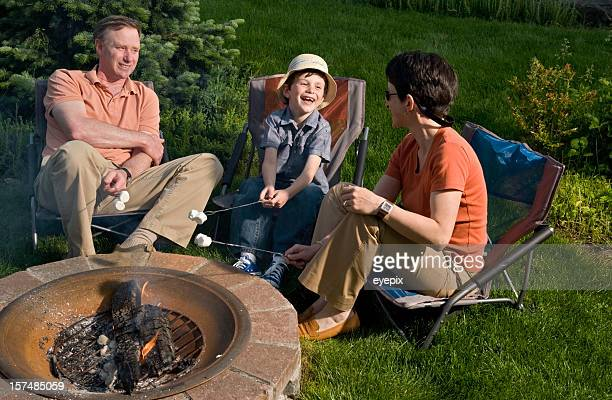 Family relaxing around fire pit