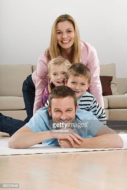 Parents with children (2-5) relaxing at home, smiling